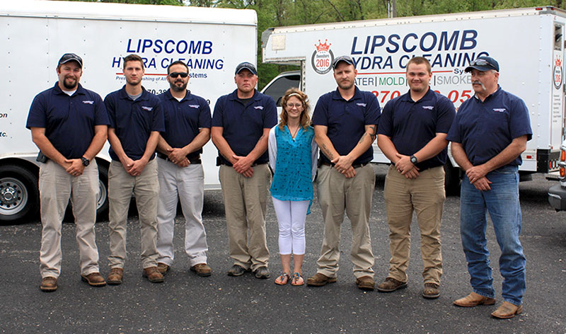 a group photo of lipscomb restoration solutions staff members standing in front of the lipscomb restoration fleet vehicles